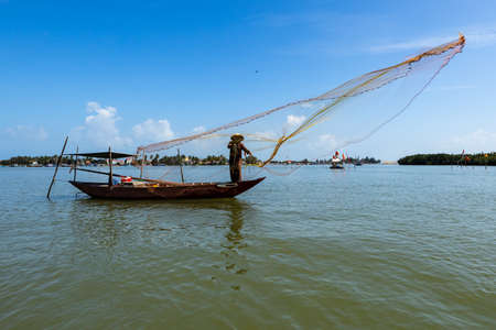 A traditional fisherman is throwing a fishing net at Hoi An in Vietnam Reklamní fotografie