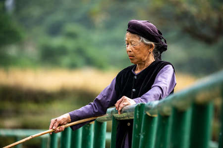 Old woman in Vietnam is fishing in a River