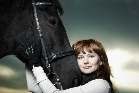 Beautiful young woman with a black horse photo