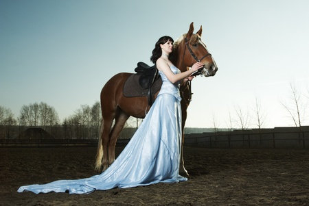 Beautiful young woman with a brown horse photo