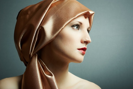 Portrait of the young girl with golden scarf on head photo