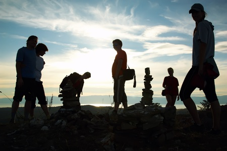 nomadic: Silhouette of group of people at top of mountain against a decline Stock Photo