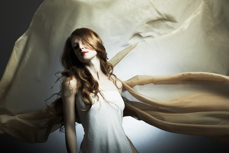Portrait of the young woman against a flying fabric photo