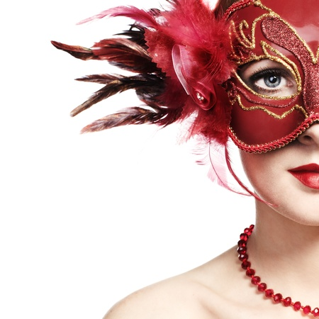 The beautiful young woman in a red mysterious venetian mask photo