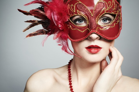 The beautiful young woman in a red mysterious venetian mask Stock Photo - 9314320