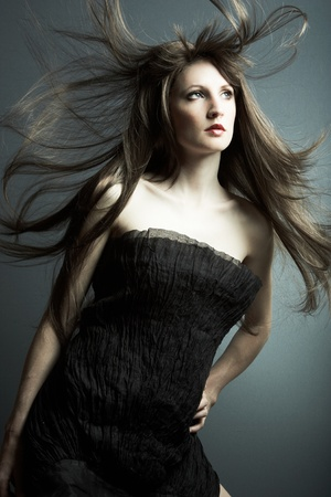 The young beautiful girl in black dress with developing hair photo