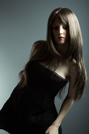 The young beautiful girl in black dress with developing hair Stock Photo - 9314273