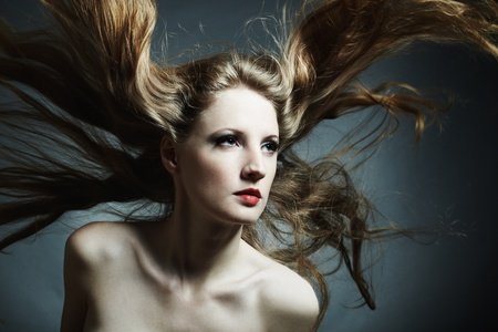Fashion portrait of the young sexy woman with flying hair photo