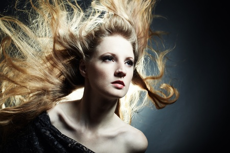Fashion portrait of the young sexy woman with flying hair Stock Photo