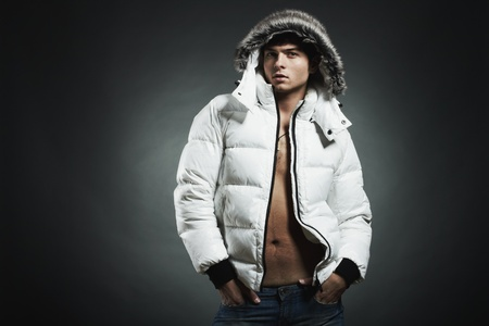 Fashion portrait of the young beautiful man in a white jacke photo