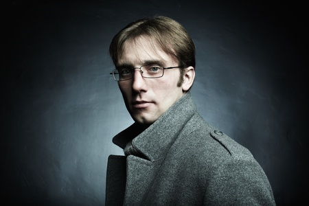 Artistic dark portrait of the young beautiful man in a gray coat photo