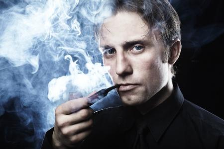 joven fumando: Retrato oscuro art�stica del joven hermoso. El joven fuma un tubo
