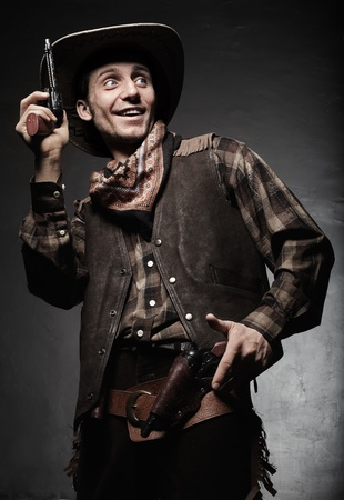 Portrait of the cowboy closeup. The smiling cowboy with pistols closeup photo