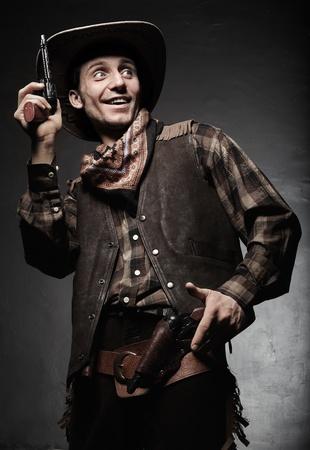 Portrait of the cowboy closeup. The smiling cowboy with pistols closeup photo