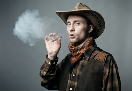 Artistic portrait of the young beautiful man. The young man smokes a cigar photo