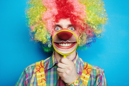 Portrait cheerful clown with the big smile on a blue background photo