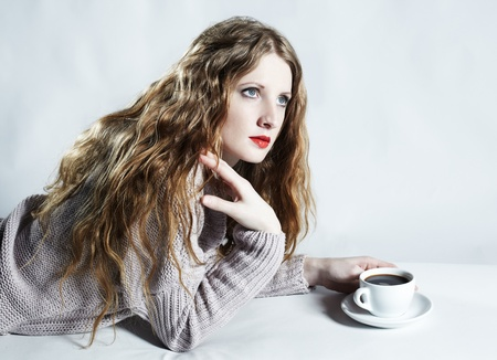 Portrait woman with a cup of coffee lying on a sofa photo
