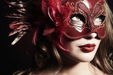Beautiful young woman in a red mysterious venetian mask Stock Photo