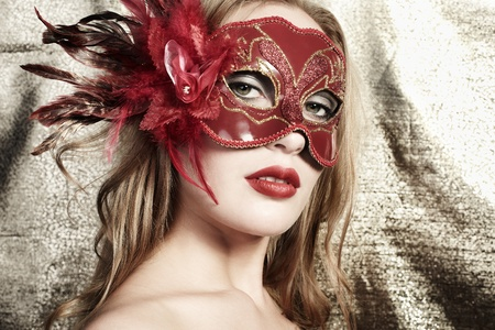Beautiful young woman in a red mysteus venetian mask on a gold background Stock Photo - 9433235