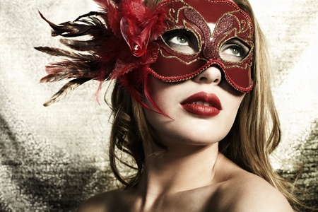 Beautiful young woman in a red mysterious venetian mask on a gold background Stock Photo
