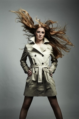 Fashion portrait of young beautiful woman in the raincoat photo
