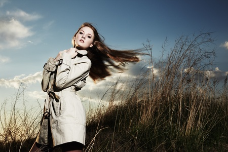 Fashion portrait of elegant woman in a raincoat on the nature photo