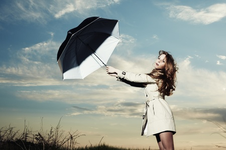 Fashion portrait of elegant woman in a raincoat on the nature. Woman with an umbrella photo