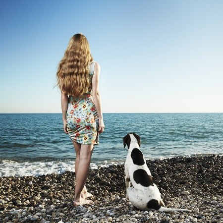 blissful: Beautiful woman with a dog on the beach
