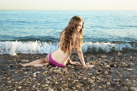 Beautiful young woman lying on the beach photo