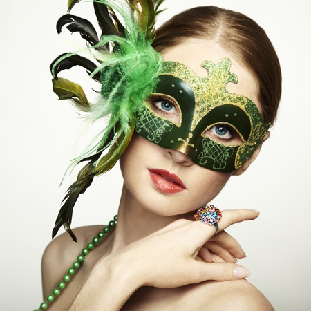 The beautiful young woman in a green mysterious venetian mask  photo