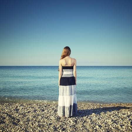 pelirrojas: Joven y bella mujer de pie en la playa. Moda en la Naturaleza Foto de archivo