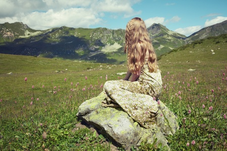 Beautiful young woman in mountains on a meadow. Fashion in Nature photo