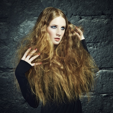 Portrait of a beautiful young woman with curly red hair. Fashion & Beauty photo