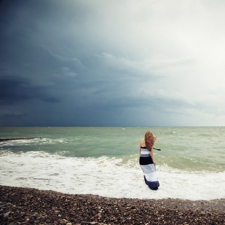 The woman on the beach during a storm  Raging ocean  photo