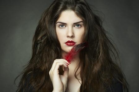 Fashion photo of woman with dark curly hair  Studio portrait photo