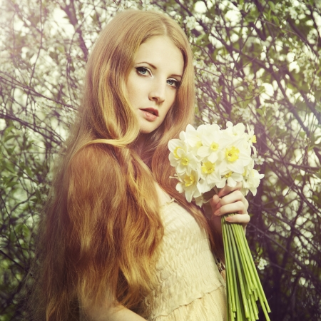 Portrait a beautiful young woman with flowers in the garden  Fashion photo photo