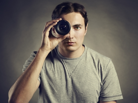 Young man photographer holding a lens in his eye  Lens as eye photo