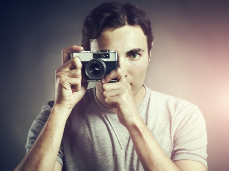Portrait of young male photographer with a camera  Man shoots at camera photo