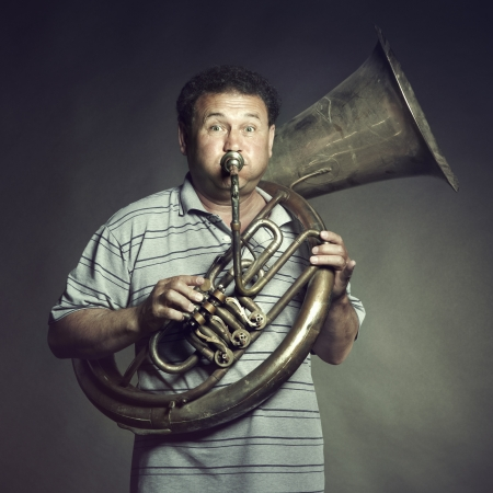 business trends: Portrait of an old man close up playing the trumpet