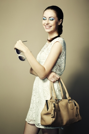 Portrait of young smiling woman with a leather bag.   photo