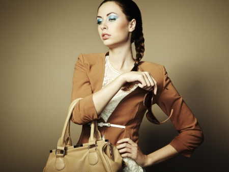 Portrait of beautiful young woman with a leather bag.   photo