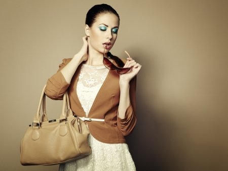 Portrait of beautiful young woman with a leather bag. Stock Photo - 15489549