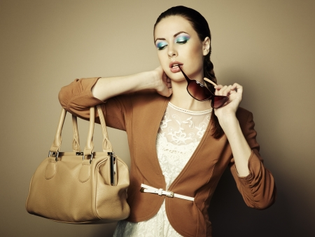 Portrait of beautiful young woman with a leather bag.