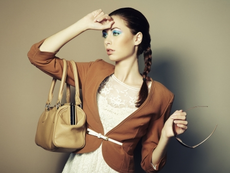 Portrait of beautiful young woman with a leather bag   photo