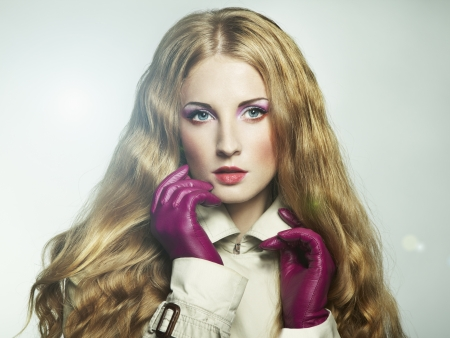 Portrait of young beautiful woman in purple gloves.
