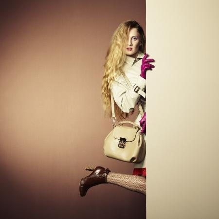 een jonge mooie vrouw in een regenjas in het interieur. Conceptuele mode Stockfoto