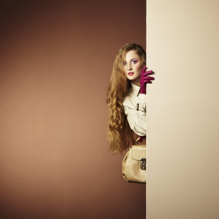 a young beautiful woman in a raincoat in interior. Conceptual fashion photo