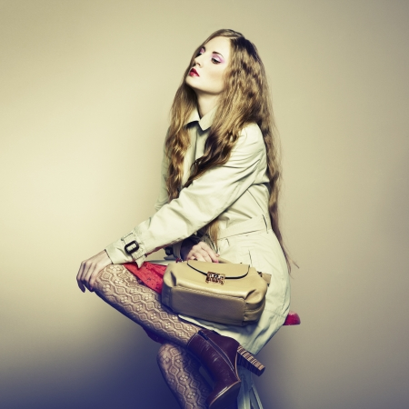 Portrait of a beautiful young woman with a handbag.  photo