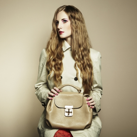 Portrait of a beautiful young woman with a handbag.