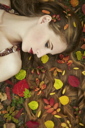 Fashion portrait of a beautiful young woman in autumn garden. Beauty autumn photo